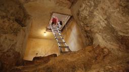 Tal mengintip lorong kolam ritual Yahudi (Mikveh) yang ditemukan di bawah tanah rumahnya di Ein Karem, Yerusalem (1/7/2015). Tal menemukan Mikveh yang diyakini berusia lebih dari 2.000 tahun saat sedang merenovasi rumah.  (AFP/GALI TIBBON)