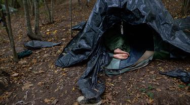 Seorang migran beristirahat di tenda yang dibuat dari lembaran plastik di kamp darurat di hutan di luar Velika Kladusa, Bosnia pada 25 September 2020. Bosnia menjadi salah satu tempat singgah para imigran dan pengungsi dalam perjalanannya ke Eropa Barat. (AP Photo/Kemal Softic)