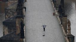 Seorang pria berselfie di Jembatan Charles yang kosong di Praha, Republik Ceko, Jumat, (20/3/2020). Pemerintah Republik Ceko telah menyetujui langkah dramatis lebih lanjut untuk mencoba dan membendung penyebaran virus corona baru yang disebut COVID-19. (AP Photo/Petr David Josek)