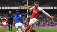 Idrisa Gueye mencoba menghentikan umpan Aaron Ramsey pada laga lanjutan Premier League yang berlangsung di Stadion Goodison Park, Liverpool, Minggu (7/4). Arsenal kalah 0-1 kontra Everton. (AFP/Oli Scarff)