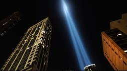 Instalasi cahaya bertajuk 'Tribute in Light'  menembak langit New York City pada Selasa (10/9/2019). Cahaya kembar berwarna biru tersebut dinyalakan untuk memperingati 18 tahun peristiwa serangan gedung kembar World Trade Center (WTC)  pada 11 September 2001 silam. (Spencer Platt/Getty Images/AFP)