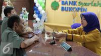 Teller tengah melayani nasabah di Bank Bukopin Syariah, Jakarta, Selasa (29/12). Namun kurs tengah Bank Indonesia mencatat rupiah menguat tipis 0,003% ke Rp 13.639 per dollar AS. (Liputan6.com/Angga Yuniar)