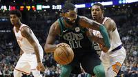 Pebasket Boston Celtics, Kyrie Irving, berusaha melewati pebasket Phoenix Suns, Tyler Ulis, pada laga NBA di Stadion TD Garden, Boston Minggu (3/12/2017). Boston Celtics menang 116-111 atas Phoenix Suns. (AP/Michael Dwyer)