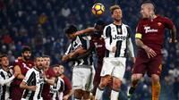 Duel udara antara pemain Juventus dan AS Roma dalam laga pekan ke-17 Serie A 2016-2017 di Juventus Stadium, Sabtu (17/12/2016) waktu setempat. (AFP/Marco Bertorello)