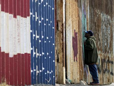 Seorang pria melihat melalui pagar perbatasan Amerika Serikat (AS) dengan Meksiko di Playas de Tijuana, Baja California, Meksiko, Minggu (11/3). Pagar perbatasan terbuat dari struktur baja setinggi sembilan meter. (GUILLERMO ARIAS/AFP)
