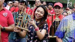 Warga memainkan angklung saat meramaikan acara 'Bangkit Indonesia' di Lokasi Car Free Day (CFD), Jakarta, Minggu (21/5). Acara memperingati Hari Kebangkitan Nasional itu dirayakan dengan pembagian 1.500 angklung. (Liputan6.com/Immanuel Antonius)
