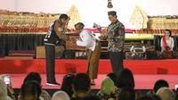 """Presiden Joko Widodo (Jokowi) bersalaman dengan dalang Ki Mantep Sudarsono (tengah) dalam Pagelaran Wayang Kulit 74 Tahun Indonesia Merdeka di halaman depan Istana Merdeka, Jakarta, Jumat (2/8/2019). Pagelaran wayang mengangkat tema """"Kresno Jumeneng Ratu"""".(Liputan6.com/Angga Yuniar)"""