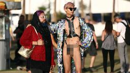 Dua penonton saat menghadiri Coachella Valley Music and Arts Festival 2018 di Empire Polo Club di Indio, Calif (15/4). Festival Coachella ini sudah ada sejak tahun 1999. (AFP Photo/Rich Fury)