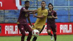 Pemain Bhayangkara Solo FC, Renan Da Silva (tengah) dijaga ketat pemain PSM Makassar, Hasim Kipuw (kiri)  dalam pertandingan matchday ke-2 Babak Penyisihan Grup B Piala Menpora 2021 di Stadion Kanjuruhan, Malang, Sabtu (27/3/2021). Kedua tim bermain imbang 1-1. (Bola.com/Ikhwan Yanuar)