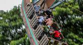 Pengunjung yang mengenakan masker menikmati wahana di taman hiburan Enchanted Kingdom di Provinsi Laguna, Filipina (18/10/2020). Taman hiburan tersebut kembali dibuka untuk pengunjung. (Xinhua/Rouelle Umali)