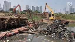 Alat berat terparkir dekat tumpukkan sampah yang muncul di permukaan Kanal Banjir Barat, Jakarta, Selasa (16/7/2019). Kemarau sejak dua bulan terakhir ini menyebabkan sampah-sampah yang mengendap di dasar sungai muncul ke permukaan sehingga menimbulkan bau tak sedap. (merdeka.com/Iqbal S Nugroho)