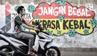 Pengendara motor melintasi mural bertema imbauan protokol kesehatan COVID-19 di kawasan Cakung Barat, Jakarta, Minggu (18/10/2020). Mural karya warga setempat tersebut bertujuan mengingatkan masyarakat akan pentingnya memakai masker, menjaga jarak, dan mencuci tangan. (merdeka.com/Iqbal S. Nugroho)