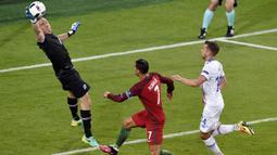 Kiper Islandia, Hannes Halldersson, menepis tendangan striker Portugal, Cristiano Ronaldo, pada laga Grup F Piala Eropa di Stadion Geoffroy Guichard, St Etienne, Rabu (14/6/2016). Islandia bermain imbang 1-1 dengan Portugal. (AFP/Jean-Philippe Ksiazek)
