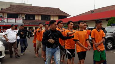 Keempat belas tersangka yang membakar dan merusak kendaraan dinas polisi, digelandang petugas Polres Metro Tangerang, Jumat (21/9/2018).