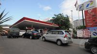 Sejumlah mobil  mengantri bahan bakar minyak di SPBU Cikini, Jakarta, Jumat (16/1/15). (Liputan6.com/Herman Zakharia)