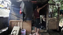 Warga bantaran menunjukkan ketinggian banjir yang merendam hingga pintu gubuk. Banjir tersebut juga menyebabkan gubuk mereka semakin rapuh dan dipenuhi sampah serta menghanyutkan barang-barang hasil pulung. (merdeka.com/Iqbal S Nugroho)