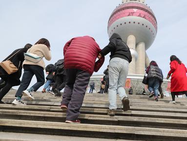 Para wisatawan bersiap memasuki Shanghai Oriental Pearl Tower di Shanghai, China, Kamis (12/3/2020). China kembali membuka bangunan ikonis Shanghai Oriental Pearl Tower, Shanghai Jinmao Tower, dan Shanghai Tower. (Xinhua/Fang Zhe)