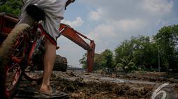 Tak ada ketakutan dalam diri bocah itu meski alat-alat berat menimbulkan suara gemuruh, Jakarta, Jumat (19/9/2014) (Liputan6.com/Faizal Fanani)
