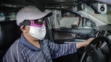 Pengemudi taksi daring, Aris Hardy Halim menunggu calon penumpang di dalam mobilnya yang telah terpasang plastik pembatas di kawasan Bendungan Hilir, Jakarta, Jumat (8/5/2020). (Liputan6.com/Faizal Fanani)