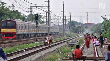 Anak-anak bermain layang-layang di rel kereta api kawasan Jakarta Timur, Kamis (3/1). Minimnya lahan terbuka hijau memaksa anak-anak setempat memilih kawasan rel kereta api sebagai lokasi bermain. (Merdeka.com/Iqbal Nugroho)
