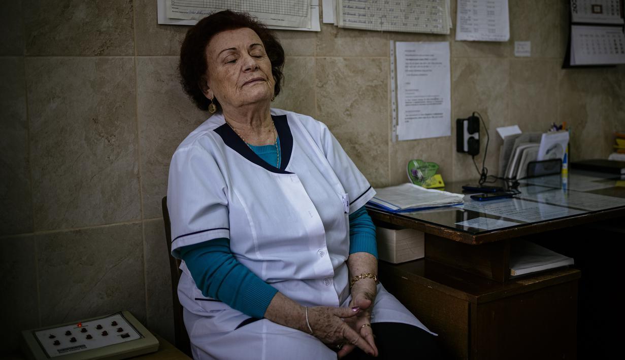 Gambar yang diambil pada 20 Januari 2021 ini menunjukkan spesialis penyakit menular Dr Maria Bogoeva (82) beristirahat sejenak saat bertugas di unit Covid-19 di sebuah rumah sakit kecil di Bulgaria. Maria Bogoeva siap untuk pensiun ketika pandemi virus corona melanda. (Dimitar DILKOFF/AFP)