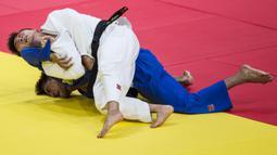 Atlet judo Kyrgyztan, Artur Te, membanting atlet judo Uzbekistan, Akhadov, pada perebutan medali perunggu cabang judo kelas 66 kg Asian Games XVIII di JCC Senayan, Jakarta, Rabu (29/8/2018). (Bola.com/Vitalis Yogi Trisna)