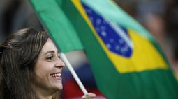 Suporter Brasil mengibaran bendera saat mendukung timnya melawan Ekuador pada laga kualifikasi Piala Dunia 2018 zona CONMEBOL di Porto Alegre, Brasil, (31/8/2017). Brasil menang 2-0.  (AP/Leo Correa)