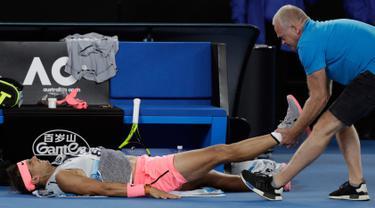 Petenis Spanyol, Rafael Nadal mendapat perawatan dari pelatihnya terkait cedera paha kanan pada perempat final Australia Terbuka 2018 di Melbourne, Selasa (23/1). Nadal mundur di set kelima saat menghadapi petenis Kroasia, Marin Cilic. (AP/Dita Alangkara)
