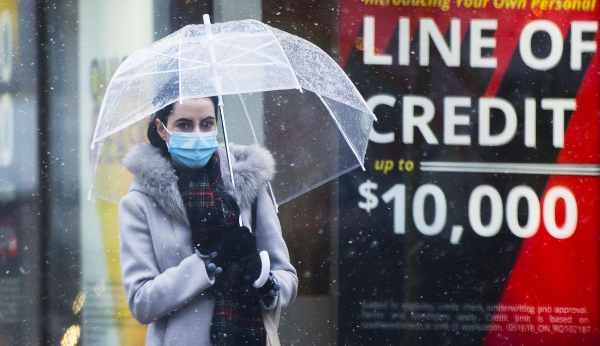Seorang wanita yang mengenakan masker melintas di sebuah jalan di Toronto, Kanada, pada 22 November 2020. Hingga Minggu (22/11) malam, Kanada melaporkan total 330.503 kasus dan 11.455 kematian karena COVID-19, menurut CTV. (Xinhua/Zou Zheng)