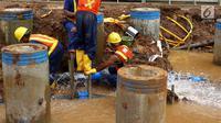 Petugas memperbaiki saluran pipa air bersih milik PAM Jaya yang bocor di kawasan proyek Jalan Layang Tol Becakayu, Jakarta, Jumat (15/12). (Liputan6.com/JohanTallo)