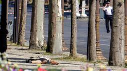 Alat pengontrol jarak jauh (kiri) memeriksa jasad seorang pria usai serangan terhadap van polisi di jalan Champs Elysees, Paris, Senin (19/6). Pria itu sengaja menabrakkan mobilnya yang berisi bahan peledak ke van milik polisi. (Thomas SAMSON / AFP)