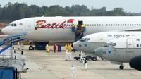 Sejumlah Warga Negara Indonesia (WNI) yang dievakuasi dari Wuhan, China keluar dari pesawat  Batik Air Airbus 330-300CEO di bandara internasional Hang Nadim, Batam, Minggu (2/2/2020). Para WNI langsung ke luar pesawat untuk selanjutnya menuju Natuna, Kepulauan Riau.  (AFP/Ricky Prakoso)