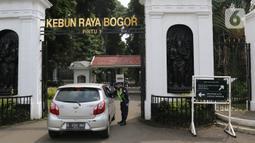 Petugas keamanan memeriksa pengunjung di Kebun Raya Bogor, Jawa Barat, Selasa (7/7/2020). Kebun Raya Bogor menerapkan pemesanan tiket secara daring serta kapasitas pengunjung dibatasi hanya 50 persen. (Liputan6.com/Herman Zakharia)
