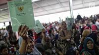 Warga menunjukkan sertifikat tanah yang baru diserahkan oleh Presiden Joko Widodo di Pusat Penerbangan Angkatan Darat, Pondok Cabe,  Tangsel, Jumat (25/1). Pada kesempatan ini, 40.172 sertifikat tanah dibagikan oleh Jokowi (Liputan6.com/Faizal Fanani)