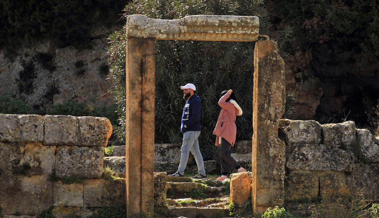 Pasangan mengunjungi situs kota Yunani kuno Kirene di pinggiran kota Libya Shehhat, di sebelah timur kota pesisir Benghazi (13/12/2019). Kirene merupakan kota tertua dan terpenting di antara lima kota Yunani yang didirikan sebagai simbol koloni bangsa Yunani di Thera sekitar 630 SM. (AFP/Abdullah Do