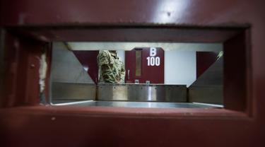 Seorang tentara AS berdiri dekat pintu sel dalam penjara Camp VI Pangkalan Angkatan Laut Teluk Guantanamo, Kuba, Rabu 17 April 2019. Penjara Guantanamo merupakan penjara paling aman dengan sekuriti yang berlapis-lapis. (AP Photo/Alex Brandon)