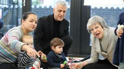 Ekspresi Perdana Menteri Inggris Theresa May saat bermain dengan bayi di pusat kesehatan di London, Inggris, Kamis (22/11). Theresa menjadi PM Inggris setelah David Cameron, PM sebelumnya, mengundurkan diri akibat Brexit. (Andrew Matthews/Pool via AP)