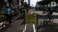 Papan pengumuman uji coba pembatas jalur sepeda permanen terlihat di kawasan Sudirman, Jakarta, Minggu (28/2/2021). Uji coba berlangsung selama tahap penyempurnaan jalur sepeda permanen yang ditargetkan rampung akhir Maret 2021. (Liputan6.com/Johan Tallo)