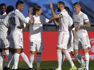 Para pemain Real Madrid merayakan gol yang dicetak oleh Karim Benzema ke gawang Valencia pada laga Liga Spanyol di Stadion Alfredo Di Stefano, Minggu (14/2/2021). Real Madrid menang dengan skor 2-0. (AP/Manu Fernandez)