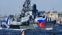 Sejumlah pelaut berjajar rapi di dek saat kapal perang Rusia berlayar selama parade Hari Angkatan Laut di Sungai Neva, Saint Petersburg, Rusia, Minggu (29/7). (Kirill Kudryavtsev/AFP)