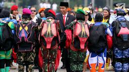 Presiden Jokowi menyapa penerjun wanita TNI seusai beratraksi pada upacara militer bersama Wanita TNI, Polwan dan Segenap Wanita Komponen Bangsa di Silang Monas Jakarta, Rabu (25/6). Upacara ini memperingati Hari Kartini 2018. (Liputan6.com/Johan Tallo)