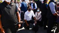 PM Kanada Justin Trudeau berlutut sebagai bentuk simpati dan dukungan, di tengah massa demonstrasi anti-rasisme dan solidaritas terhadap George Floyd di Kanada pada Jumat 5 Juni 2020 (AP Photo)