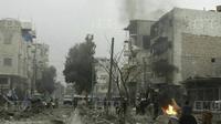 Relawan White Helmets memadamkan kobaran api bekas serangan militer di Provinsi Idlib, Suriah, Minggu, (7/1). Laporan mengatakan bahwa ledakan merupakan bom mobil, sementara lainnya menyebut serangan drone. (Syrian Civil Defense White Helmets via AP)