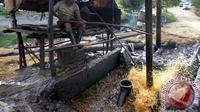 Penambang tradisional menuang minyak mentah menggunakan timba besi. (Antara Foto/Aguk Sudarmojo)