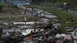 Orang-orang berkumpul di sungai untuk mendinginkan diri ketika suhu mencapai 40 derajat celsius di Islamabad, Pakistan pada Rabu (27/5/2020). Banyak kota di Pakistan menghadapi kondisi gelombang panas dengan suhu mencapai 50 derajat celsius di beberapa tempat.  (AP Photo/Anjum Naveed)