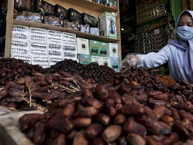 Pedagang menata kurma dagangannya di Pasar Tanah Abang, Jakarta, Rabu (22/4/2020). Pandemi COVID-19 membuat lesu penjualan kurma, keuntungan pedagang menurun hingga 80 persen lebih padahal pada tahun sebelumnya menjelang Ramadan biasanya ramai pembeli. (Liputan6.com/Johan Tallo)