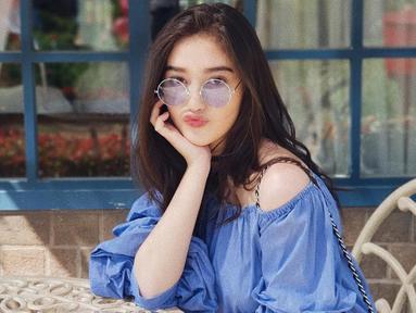 Kacamata bulat berlensa biru ini pun disesuaikan dengan busana off shoulder yang dikenakan. Gaya sederhana Ranty Maria ini pun bisa jadi inspirasi saat liburan. (Liputan6.com/IG/@rantymaria)