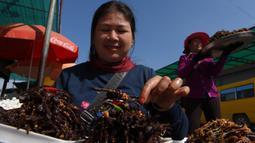 """Pedagang Kamboja menyiapkan tarantula goreng untuk dijual di wilayah Skun, Provinsi Kampong Cham, 4 Desember 2019. Daerah yang kerap dijuluki """"Spiderville"""" tersebut menjadi tempat menarik bagi para turis berburu aping, camilan tradisional dari tarantula ini. (TANG CHHIN Sothy / AFP)"""