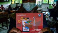 Warga penerima manfaat menunjukan buku tabungan usai mengambil Bantuan Sosial Tunai (BST) di SDN Kembangan Utara 05 Pagi, Jakarta, Rabu (31/3/2021). Program BST sebesar Rp300 ribu dari Kemensos ini disalurkan melalui RT-RT se kelurahan Kembangan Utara melalui ATM Bank DKI. (Liputan6.com/Johan Tallo)