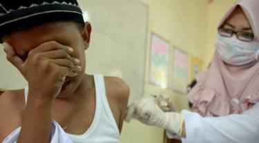 Siswa MIN Ulee Kareng menutup wajah saat mendapat vaksinasi anti virus difteri yang diberikan petugas Kesehatan di Banda Aceh, Aceh, Selasa (20/2). Dari catatan Dinkes, difteri kerap menyerang manusia kisaran usia 4 - 28 tahun. (CHAIDEER MAHYUDDIN/AFP)